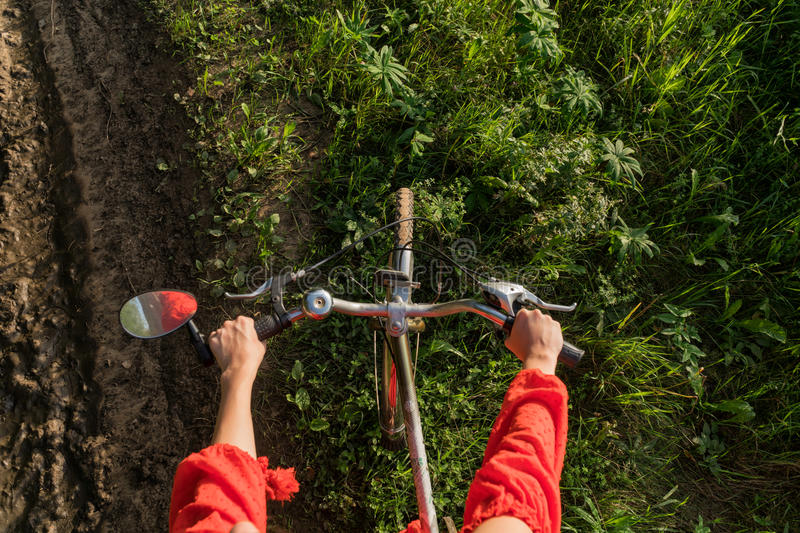 The girl holds onto the wheel of the bicycle. View from above stock photo