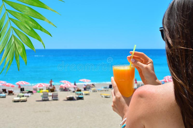 Girl holds orange fresh juice in her hand. Blue sea and beach on a backdrop.  royalty free stock photo