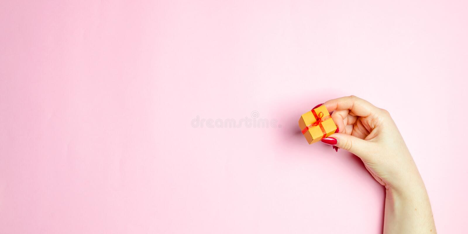 The girl holds out a gift on a pink background. Concept gift for your loved one on Valentine`s Day. Make it nice to pick the righ royalty free stock photography