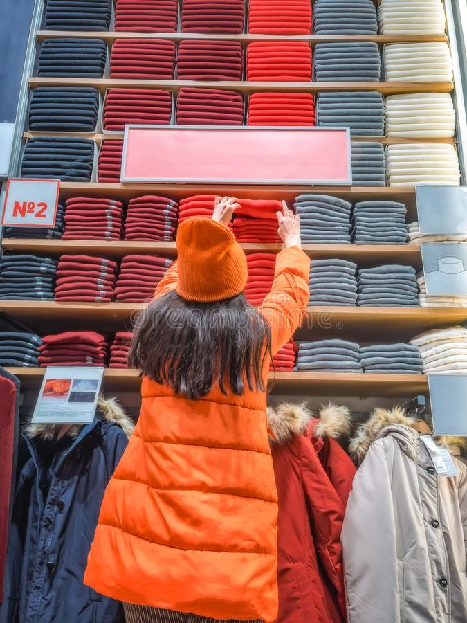The girl holds out her hand for clothes on the store shelf. shopper pulls on a thing in a clothing store. Rear view of stock photography