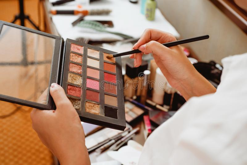 The girl holds a palette of shadows for make-up stock photo
