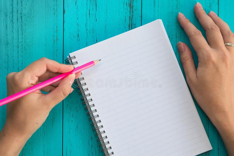 Girl holds pencil in left hand, prepares to write down goals for future in notebook, blue wooden table. Education, study, goals royalty free stock photography