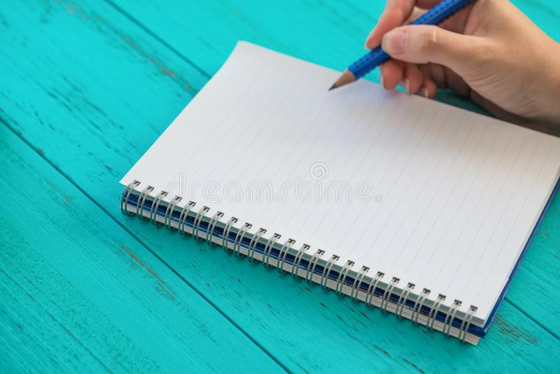 Girl holds pencil, prepares to write down goals for future in notebook, blue wooden table. Education and goals concept background stock photos
