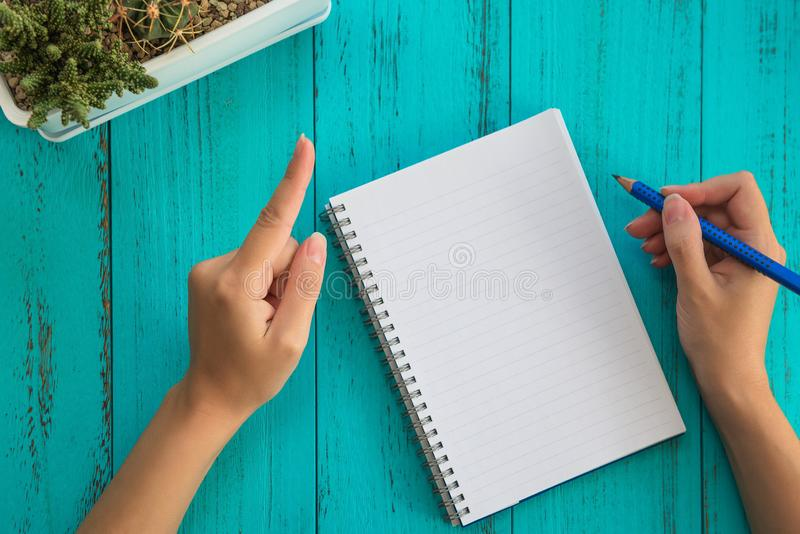 Girl holds pencil, prepares to write down goals for future in notebook, blue wooden table. Education and goals concept background. Top view stock image