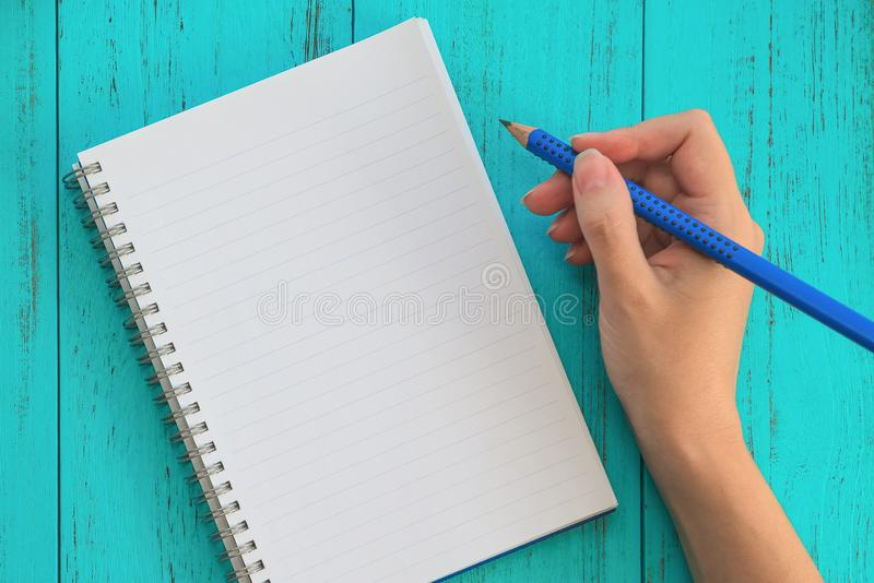 Girl holds pencil, prepares to write down goals for future in notebook, blue wooden table. Education, study, goals concept stock photo