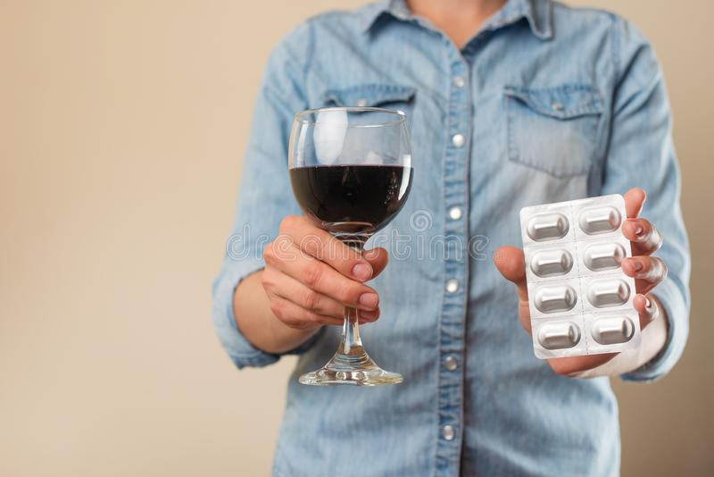 A girl holds a pill with a glass of wine, a ban on drugs for alcohol, the choice of treatment or alcohol.  royalty free stock image