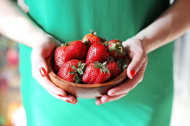 Girl holds a plate of red fresh strawberry royalty free stock images