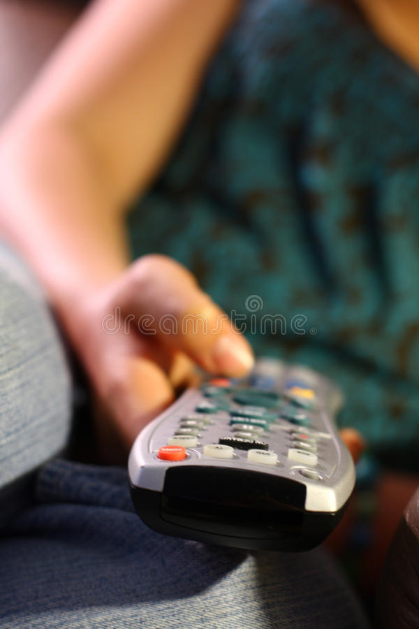 Girl holds remote control for TV. A girl holds a remote controller for the television (TV). Blurred background royalty free stock images
