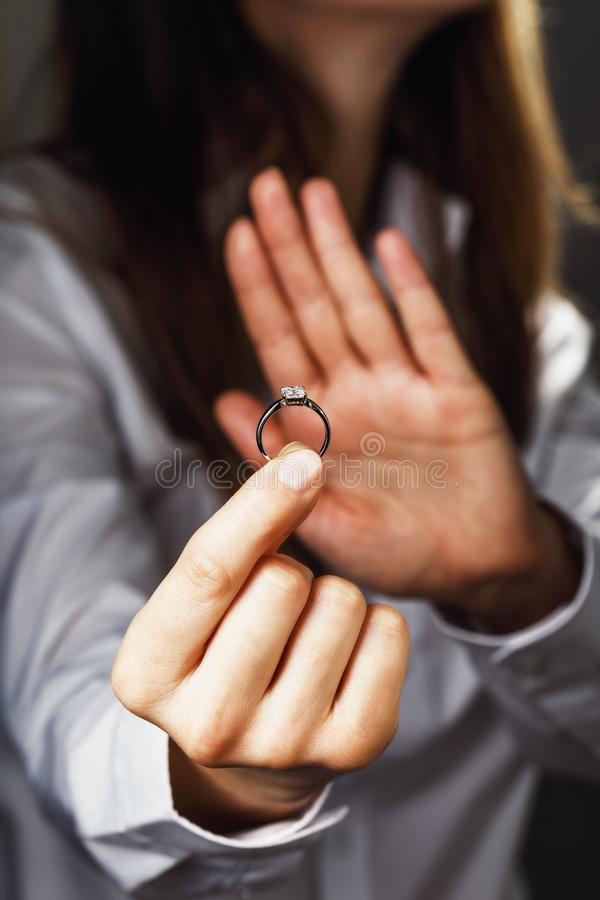 Girl holds a ring with diamond. Concept on refusal in an engagement royalty free stock photography