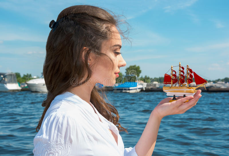 Girl holds a small ship with red sails. Modern Assol. Girl holds a small ship with red sails. Modern Assol near the water royalty free stock photography