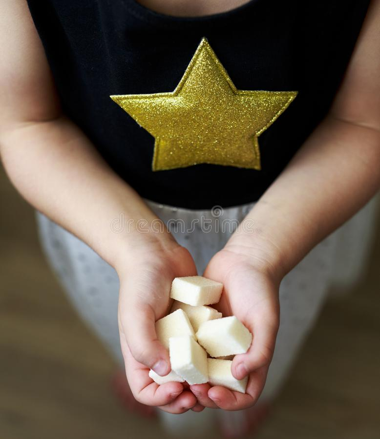 The girl holds the sugar cubes. stock photography