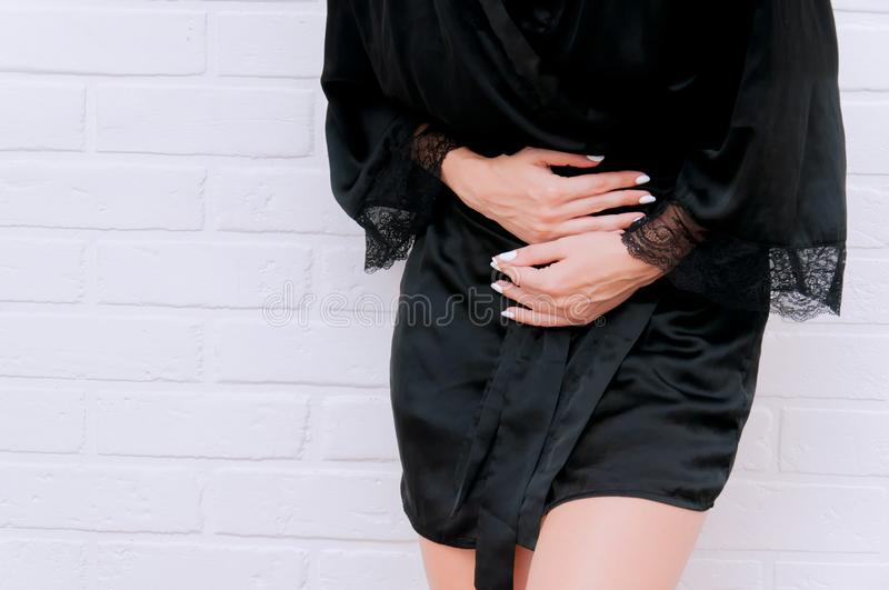 A girl holds on to her stomach in a black coat against a white wall. The girl has abdominal pain royalty free stock image