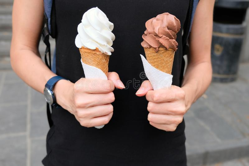 A girl holds two ice cream cones chocolate and white. Delicious ice cream is the best dessert in the summer stock images