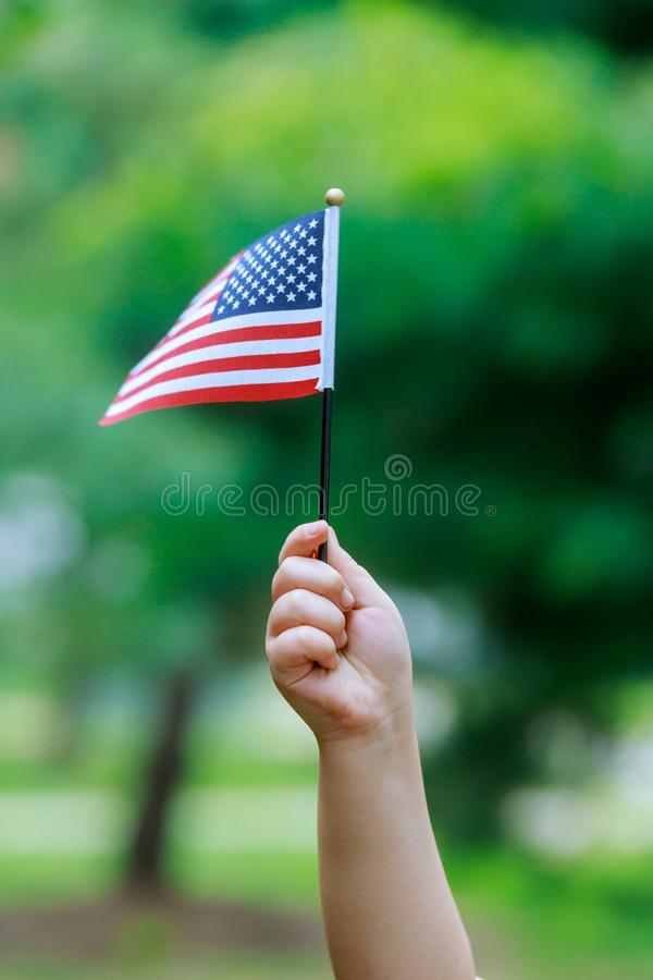The girl holds the US flag in her hands. Close-up. The girl holds the US american flag in her hands. Close-up stock photo