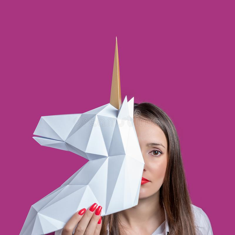 The girl holds a white 3d papercraft model of Unicorn. Minimal Art concept.  royalty free stock images