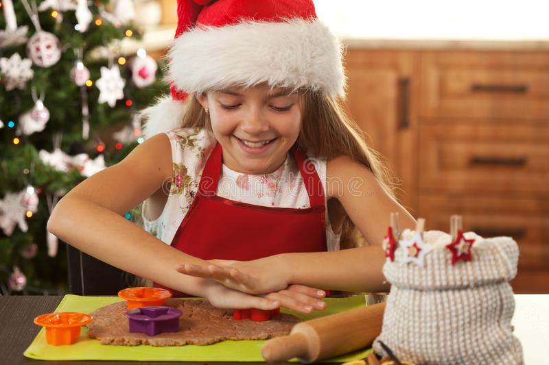 Girl in holidays mood making gingerbread cookies - cutting dough royalty free stock photography