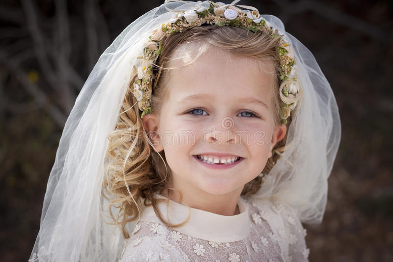 Girl in holy communion dress and veil stock images