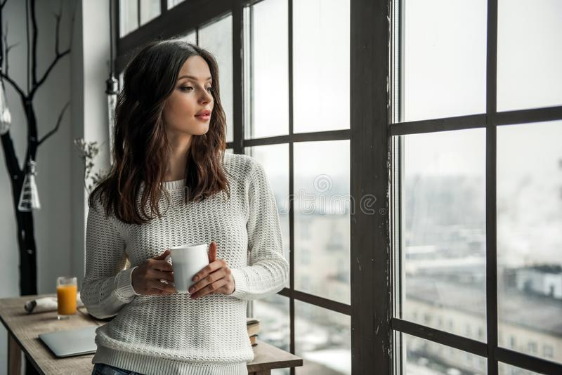 Girl at home. Beautiful young girl in casual clothes is holding a cup and looking out the window while leaning on the wooden table at home stock image