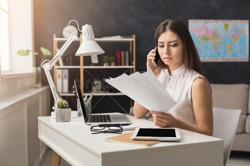 Girl at home working on laptop and talking on mobile stock photography