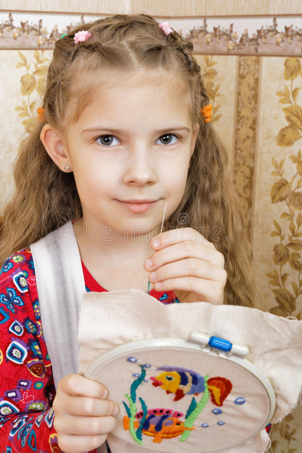 Girl with a homemade embroidery. Seven-year girl with a homemade embroidery stock photography
