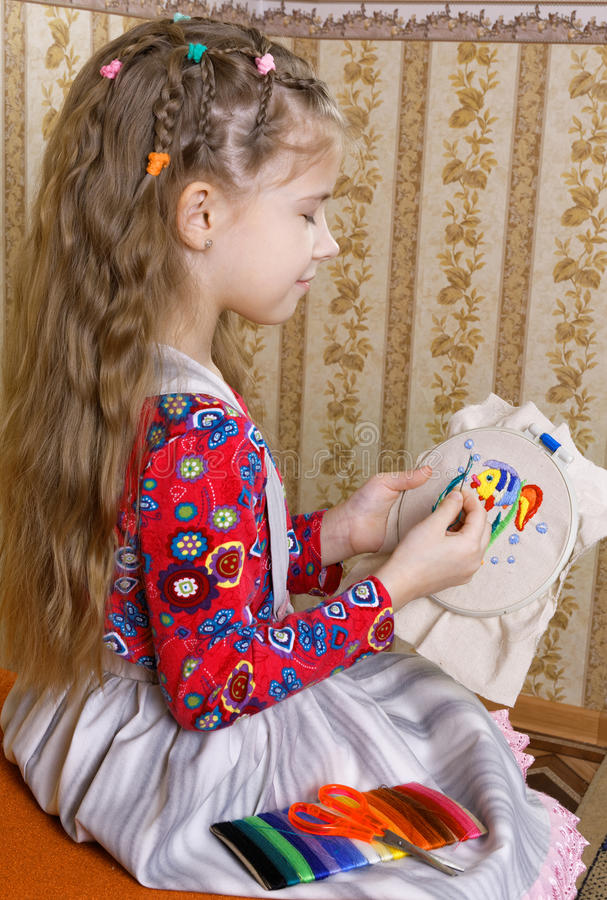 Girl with a homemade embroidery. Seven-year girl with a homemade embroidery stock images