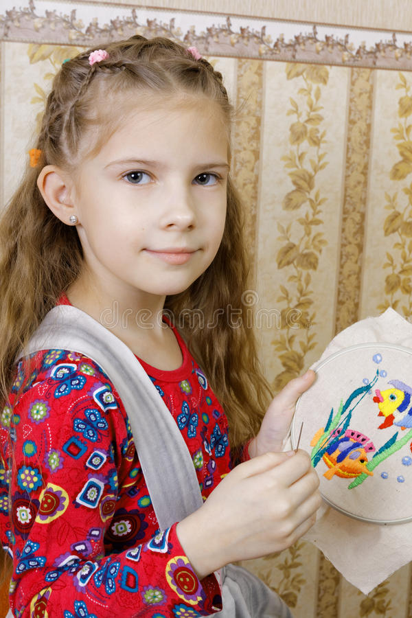 Girl with a homemade embroidery. Seven-year girl with a homemade embroidery royalty free stock photography