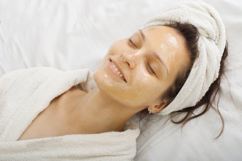 Girl with a honey facialmask royalty free stock photo