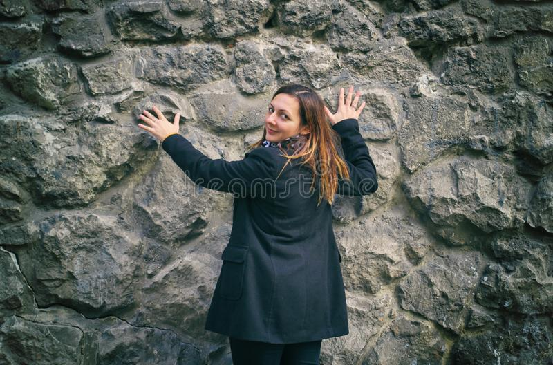 Girl in hood and coat with baggage near stone wall in autumn season. girl near the stone wall stock photos