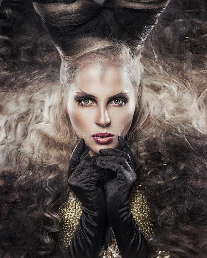 The girl with the horns. Beautiful girl with horns and curly hair in artistic style in gold suit with black feathers stock photo