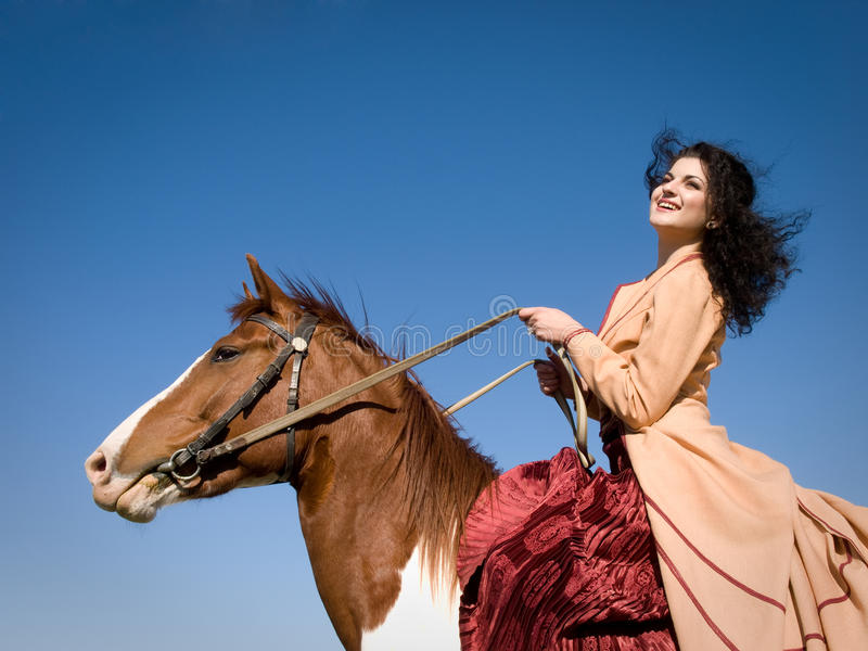 Girl on a horse. Beautiful girl in retro dress sitting on a horse against blue sky royalty free stock images