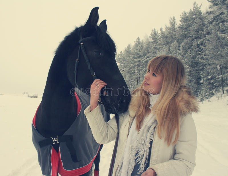 Girl with a horse. Blonde girl with a horse in the winter forest stock image