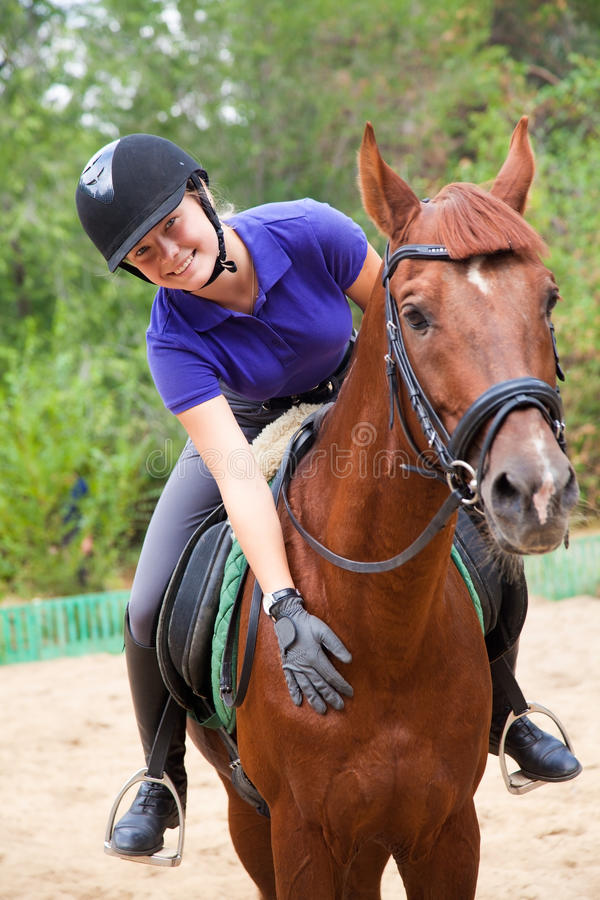 Girl with horse. Portrait of young horsewoman and brown horse royalty free stock photo