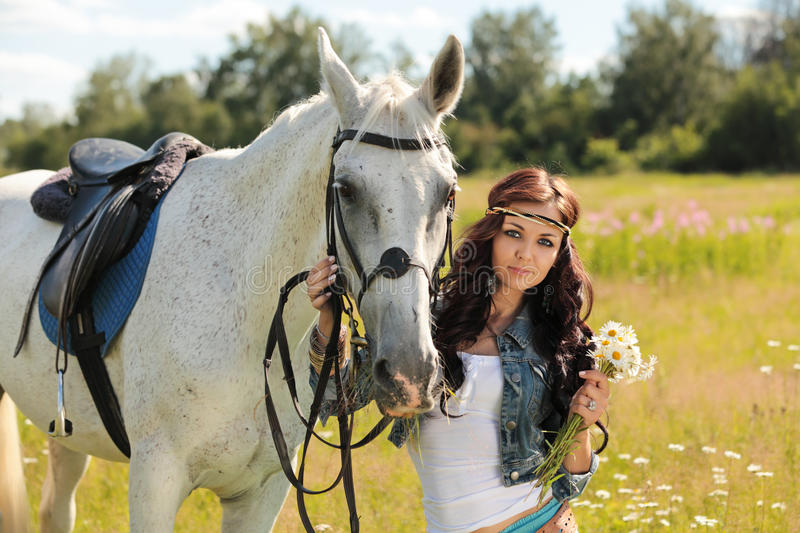 Girl with horse. Beautiful girl walks on white horse on a summer meadow royalty free stock images