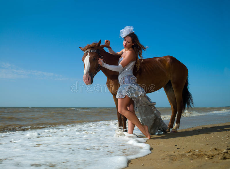 Girl and horse at the beach stock photo