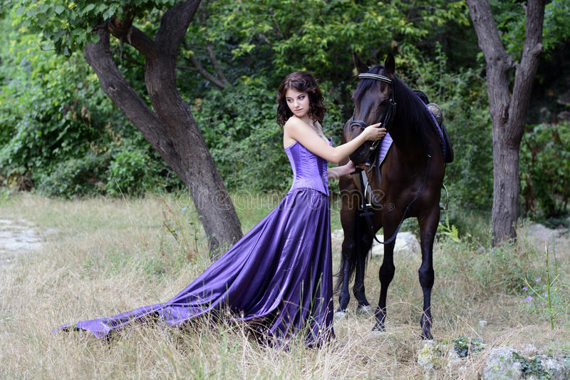 Girl with a horse. The girl in a beautiful dress with a horse in the fairy forest stock photos