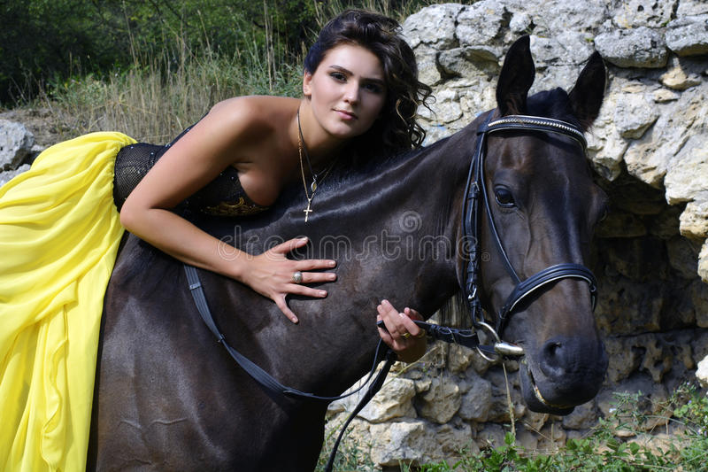 Girl with a horse. The girl in a beautiful dress with a horse in the fairy forest royalty free stock photo