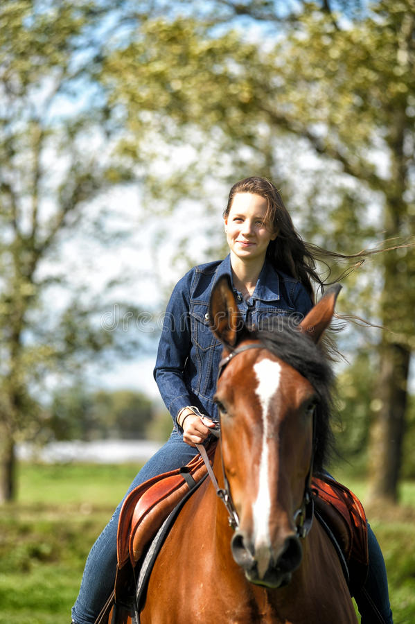 Girl on a horse. Girl in jeans suit on a horse royalty free stock photography