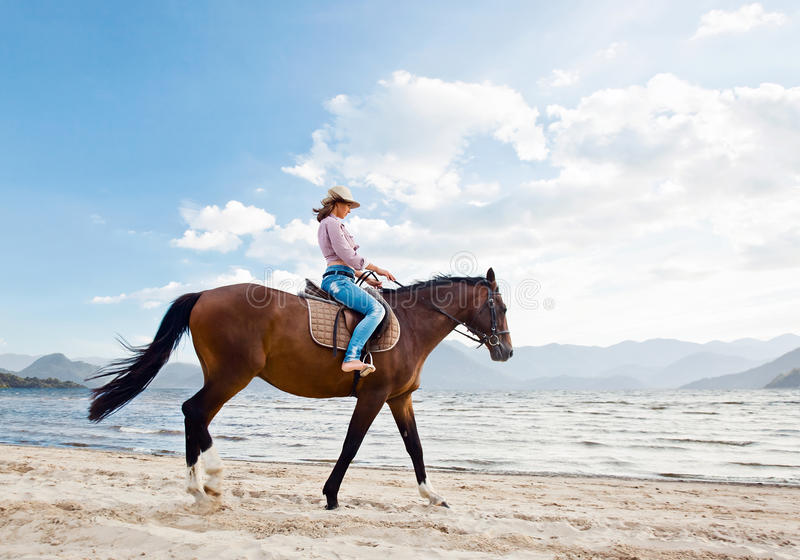 Girl with horse on seacoast stock photos