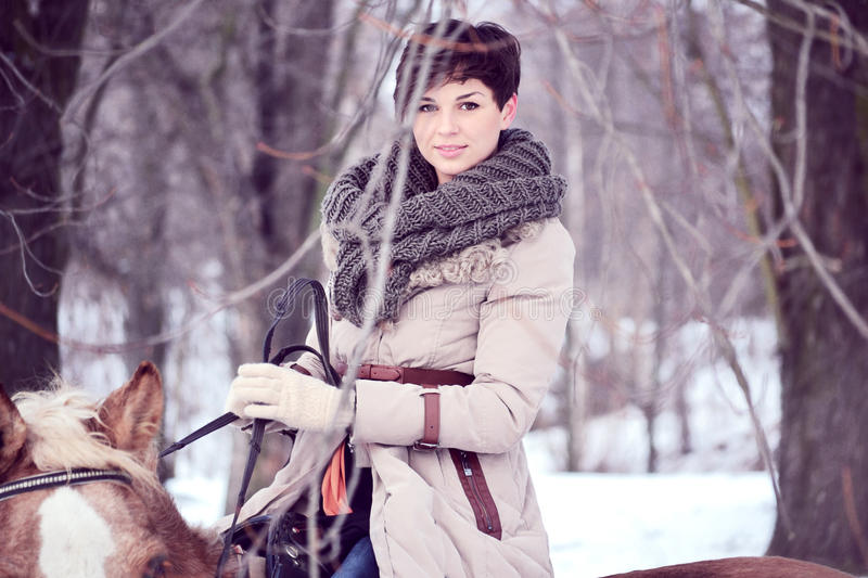 Girl in horse in winter stock photography