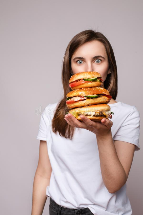 Girl with huge hamburger on hand.Studio portrait of young brunette woman in white t-shirt holding enormous burgers on stock photo