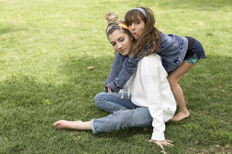 Girl hugging behind her sister. royalty free stock photography