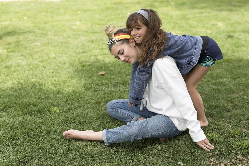 Girl hugging behind her sister. royalty free stock images