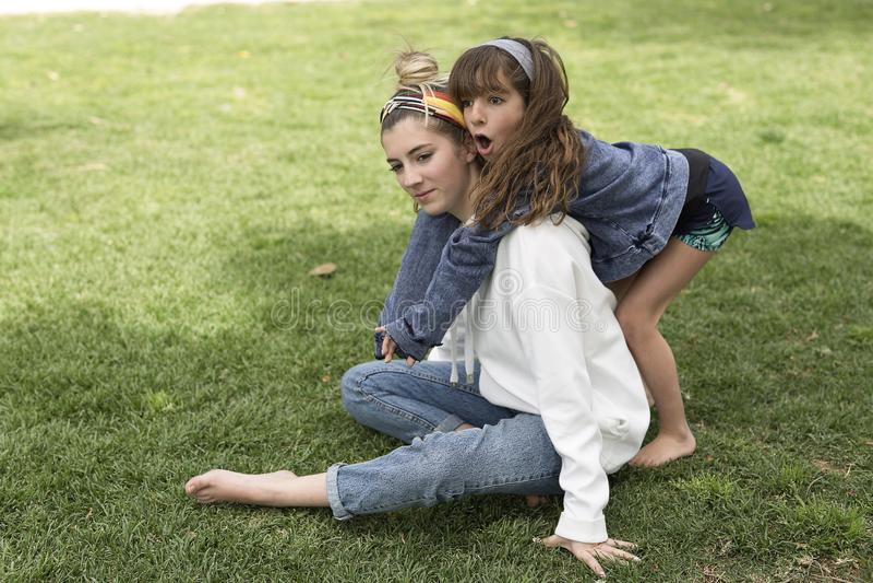 Girl hugging behind her sister. royalty free stock image