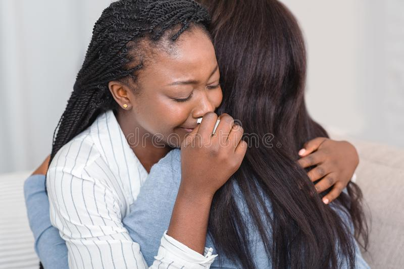 Girl hugging and consoling her crying friend at home stock photography
