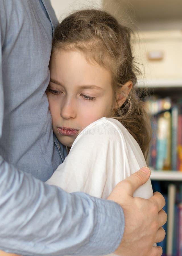 Girl hugging her dad. Sad little girl hugging her dad stock images