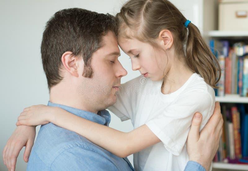 Girl hugging her dad. Sad little girl hugging her dad royalty free stock photography