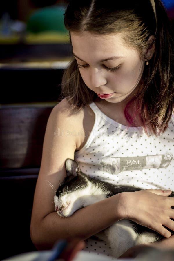 Girl hugging a stray kitten. Girl loving and caring for a stray kitten