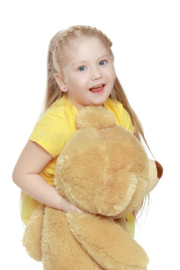 Girl hugs a big teddy bear. A lovely little round-faced blonde girl, with very long beautiful hair, in short skirts and yellow jerseys.She hugs a big teddy bear royalty free stock photography