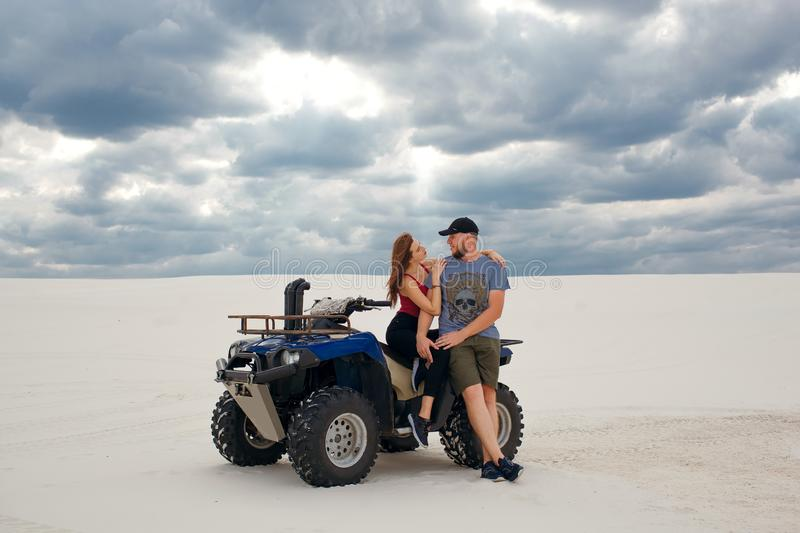 Girl hugs her boyfriend on a quad in the desert, a loving couple enjoys each other royalty free stock photo