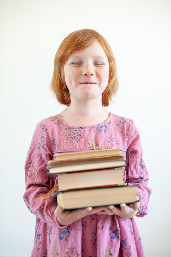 The girl hugs her favorite book. The redhead girl hugs her favorite book stock photo